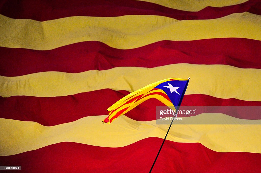 A Catalonian pro-indepence flag flies overa Catalan flag prior to a friendly match between Catalonia and Nigeria at Cornella-El Prat Stadium on January 2, 2013 in Barcelona, Spain.