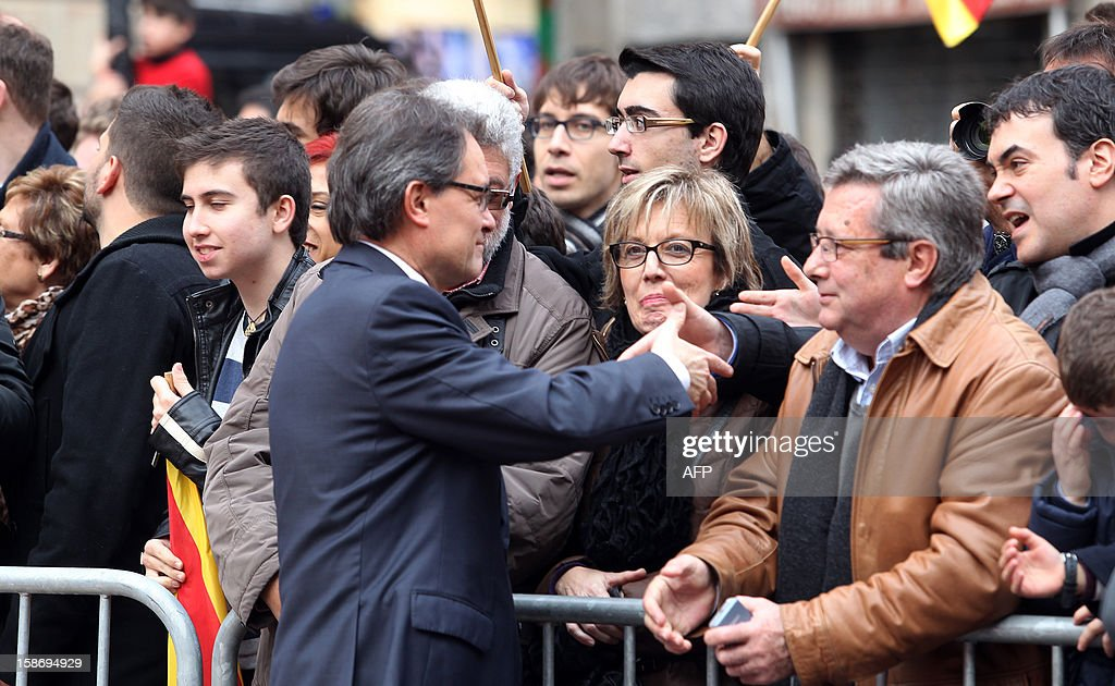 Catalonia's president Artur Mas (L) shakes hands with his supporters after his swearing-in ceremony in Barcelona on December 24, 2012. AFP PHOTO / QUIQUE GARCIA