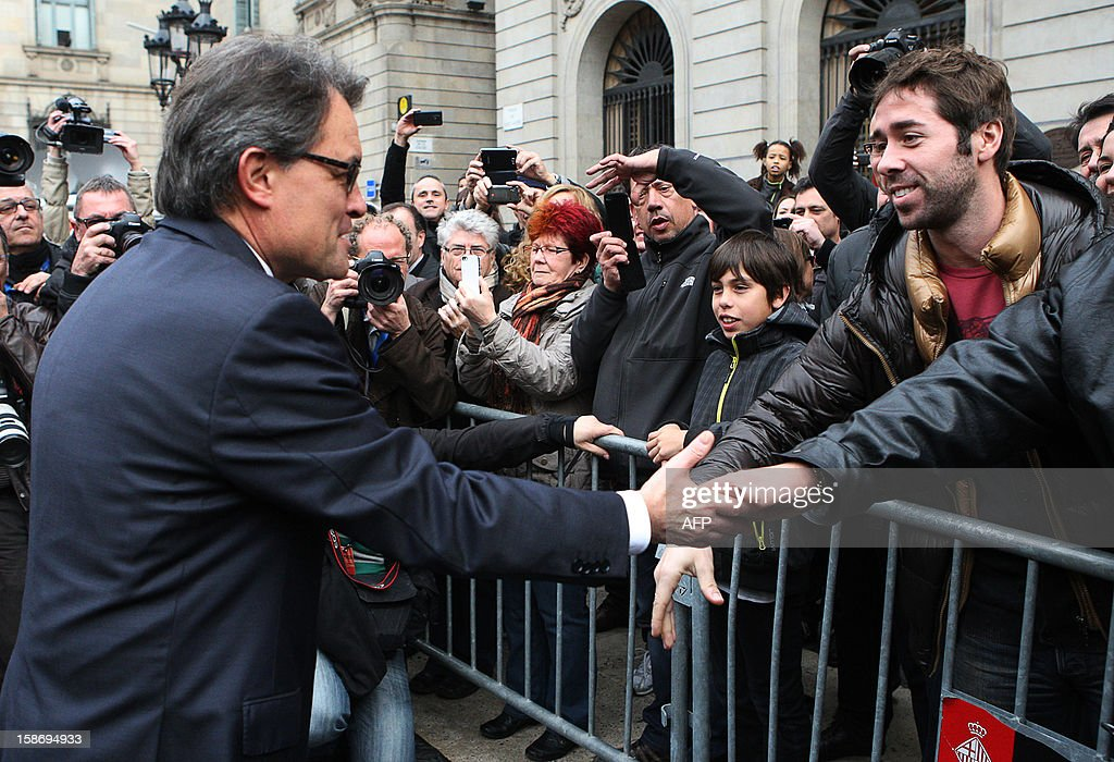 Catalonia's president Artur Mas (L) shakes hands with his supporters after his swearing-in ceremony in Barcelona on December 24, 2012.