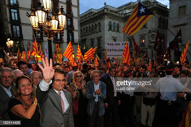 Catalonia's regional president Artur Mas and his wife Elena Rakosnic wave to a crowd of supporters holding Catalan independist flags upon their...