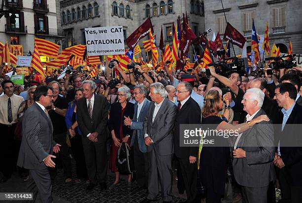 Catalonia's regional president Artur Mas is greeted by supporters holding Catalan independist flags upon his arrival at the Plaza Sant Jaume square...