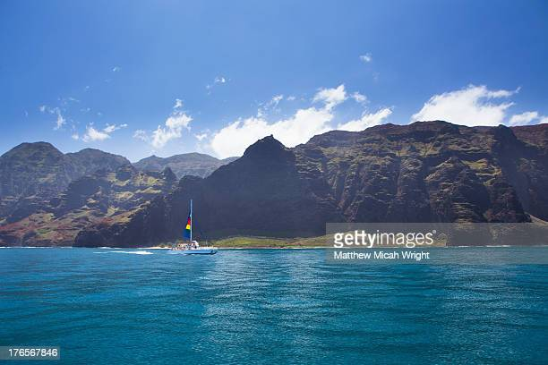 A catamaran cruises along the Napali coast.