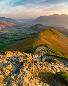 Vibrant sunrise colours with golden light on rocks in the foreground taken in the English Lake District on a spring morning.
