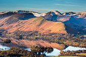 A view of Catbells mountain reflecting in Derwentwater at sunrise, Cumbria, Lake District, England.