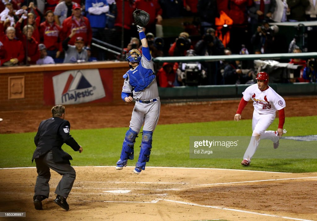 Catcher A.J. Ellis #17 of the Los Angeles Dodgers leaps after the ball thrown by Yasiel Puig #66 as <a gi-track='captionPersonalityLinkClicked' href=/galleries/search?phrase=David+Freese+-+Baseball+Player&family=editorial&specificpeople=4948315 ng-click='$event.stopPropagation()'>David Freese</a> #23 of the St. Louis Cardinals comes around to score in the third inning in Game Six of the National League Championship Series at Busch Stadium on October 18, 2013 in St Louis, Missouri.