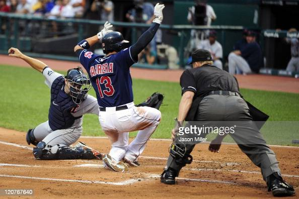 Catcher Alex Avila of the Detroit Tigers miss the tag on Asdrubal Cabrera who scored on a sacrifice fly by Carlos Santana of the Cleveland Indians...