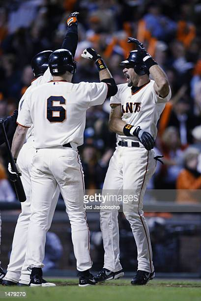 Catcher Benito Santiago of the San Francisco Giants celebrates with teammates JT Snow and Barry Bonds after hitting a two RBI home run in the eighth...