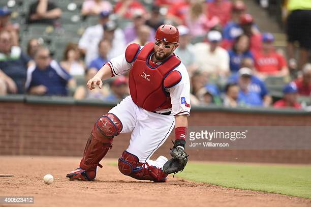 Catcher Bobby Wilson of the Texas Rangers slides to his knees as he retrieves a wild pitch in the game against the Seattle Mariners at Globe Life...