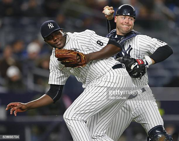 Catcher Brian McCann of the New York Yankees attempts to throw over pitcher Michael Pineda to throw out Hanley Ramirez of the Boston Red Sox who beat...