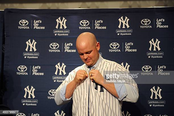 Catcher Brian McCann puts on his Yankee jersey during his introductory press conference at Yankee Stadium on December 5 2013 in the Bronx borough of...