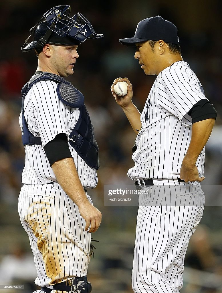 Catcher Brian McCann talks with Hiroki Kuroda of the New York Yankees walks off the mound in the seventh inning against the Boston Red Sox in a MLB...