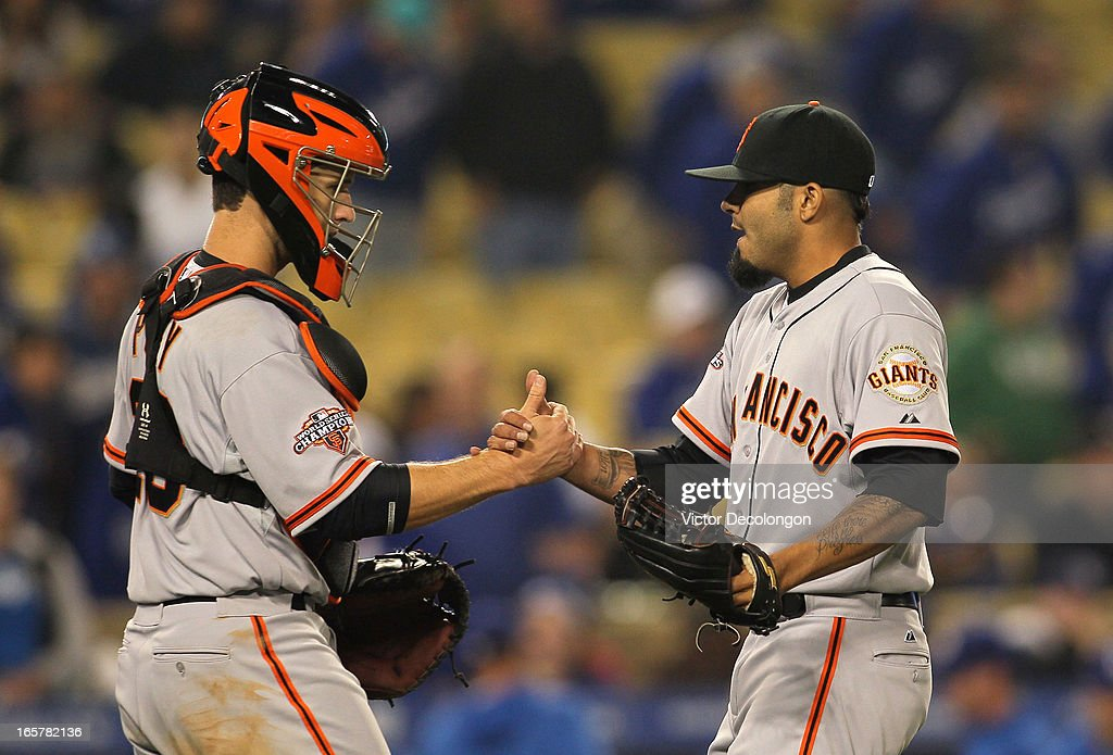 Catcher Buster Posey #28 and relief pitcher Sergio Romo #54 of the San Francisco Giants shake hands after their MLB game against the Los Angeles Dodgers at Dodger Stadium on April 3, 2013 in Los Angeles, California. The Giants defeated the Dodgers 5-3.