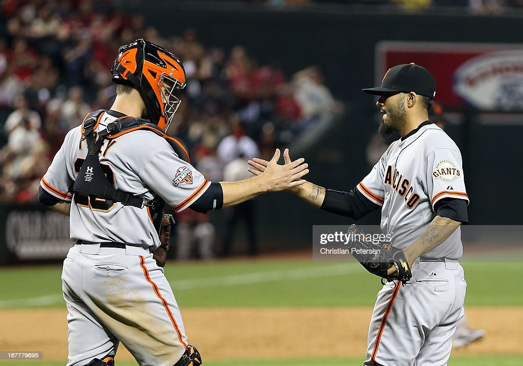 Catcher Buster Posey #28 and relief pitcher Sergio Romo #54 of the San Francisco Giants celebrate after defeating the Arizona Diamondbacks 6-4 in the MLB game at Chase Field on April 29, 2013 in Phoenix, Arizona.