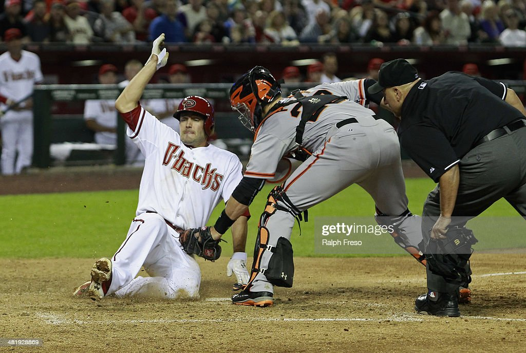Catcher <a gi-track='captionPersonalityLinkClicked' href=/galleries/search?phrase=Buster+Posey&family=editorial&specificpeople=4896435 ng-click='$event.stopPropagation()'>Buster Posey</a> #28 of the San Francisco Giants applies a late tag as A.J. Pollock #11 of the Arizona Diamondbacks slides across the plate to score a run during the sixth inning of a MLB game at Chase Field on April 1, 2014 in Phoenix, Arizona.