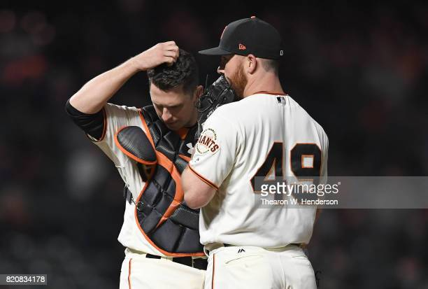 Catcher Buster Posey of the San Francisco Giants comes out to talk with pitcher Sam Dyson afte Dyson walked Edwin Encarnacion of the Cleveland...