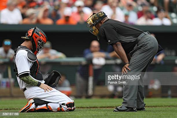 Catcher Caleb Joseph of the Baltimore Orioles kneels injured after taking a pitcher to the groin against the Boston Red Sox at Oriole Park at Camden...