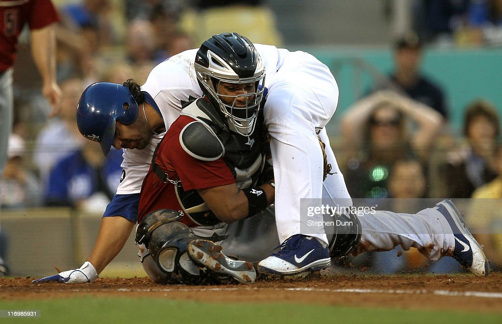 Catcher Carlos Corporan #22 of the Houston Astros tags out Rod Barajas #28 of the Los Angeles Dodgers in a collision at home plate to end the second inning on June 18, 2011 at Dodger Stadium in Los Angeles, California.