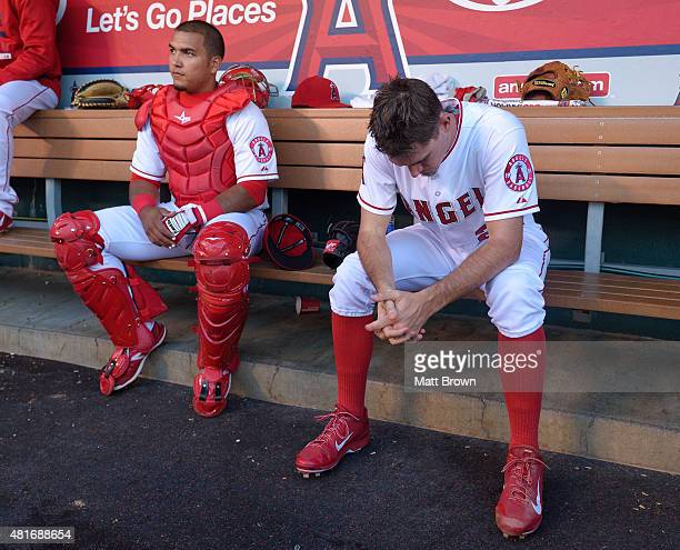 Catcher Carlos Perez and starting pitcher Andrew Heaney of the Los Angeles Angels of Anaheim sit in the dugout before the game against the Boston Red...