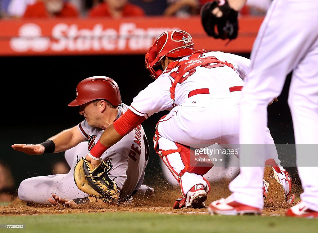 Catcher Carlos Perez #58 of the Los Angeles Angels of Anaheim tags out <a gi-track='captionPersonalityLinkClicked' href=/galleries/search?phrase=Cliff+Pennington+-+Baseball+Player&family=editorial&specificpeople=8134145 ng-click='$event.stopPropagation()'>Cliff Pennington</a> #4 of the Arizona Diamondbacks as Pennington tries to score on a base hit for the third out of the top of the seventh inning at Angel Stadium of Anaheim on June 15, 2015 in Anaheim, California.