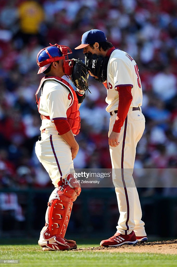 Catcher Carlos Ruiz and starting pitcher Cole Hamels of the Philadelphia Phillies talk on the pitcher's mound against the Colorado Rockies in Game...