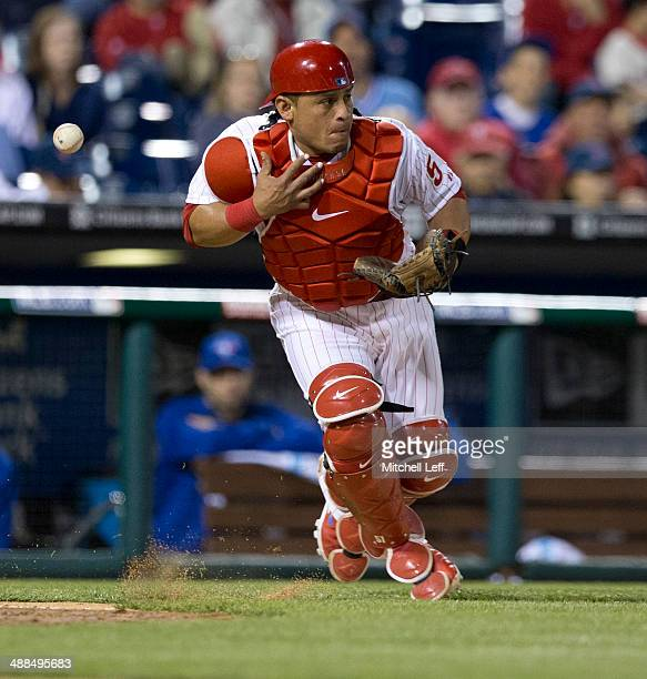Catcher Carlos Ruiz of the Philadelphia Phillies attempts to throw out a runner at second base but drops the ball in the top of the tenth inning...
