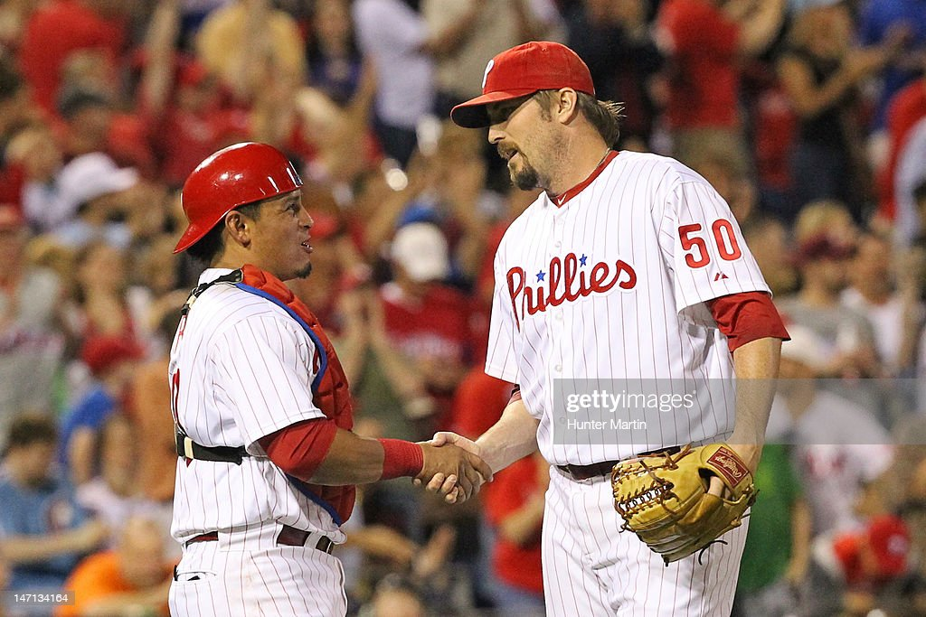 Catcher Carlos Ruiz #51 of the Philadelphia Phillies congratulates relief pitcher Chad Qualls #50 after recording the final out of a game against the Pittsburgh Pirates at Citizens Bank Park on June 25, 2012 in Philadelphia, Pennsylvania. The Phillies won 8-3.