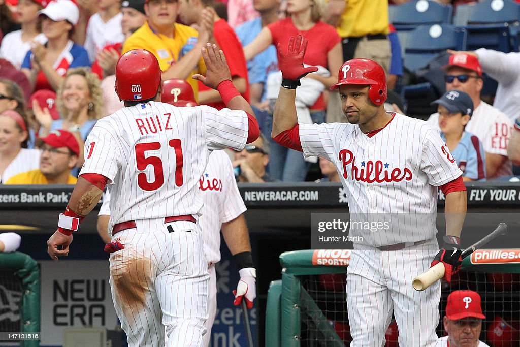 Catcher Carlos Ruiz #51 of the Philadelphia Phillies is congratulated by third baseman Placido Polanco #27 after scoring a run during a game against the Pittsburgh Pirates at Citizens Bank Park on June 25, 2012 in Philadelphia, Pennsylvania.
