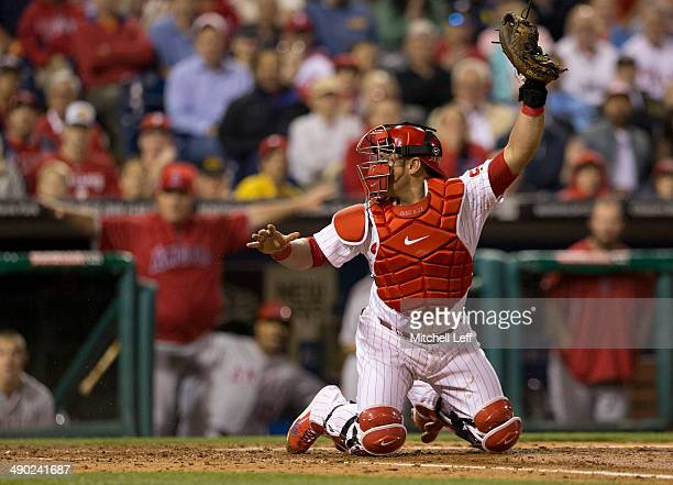 Catcher Carlos Ruiz of the Philadelphia Phillies is pulled off home plate trying to make an out in the top of the sixth inning against the Los...