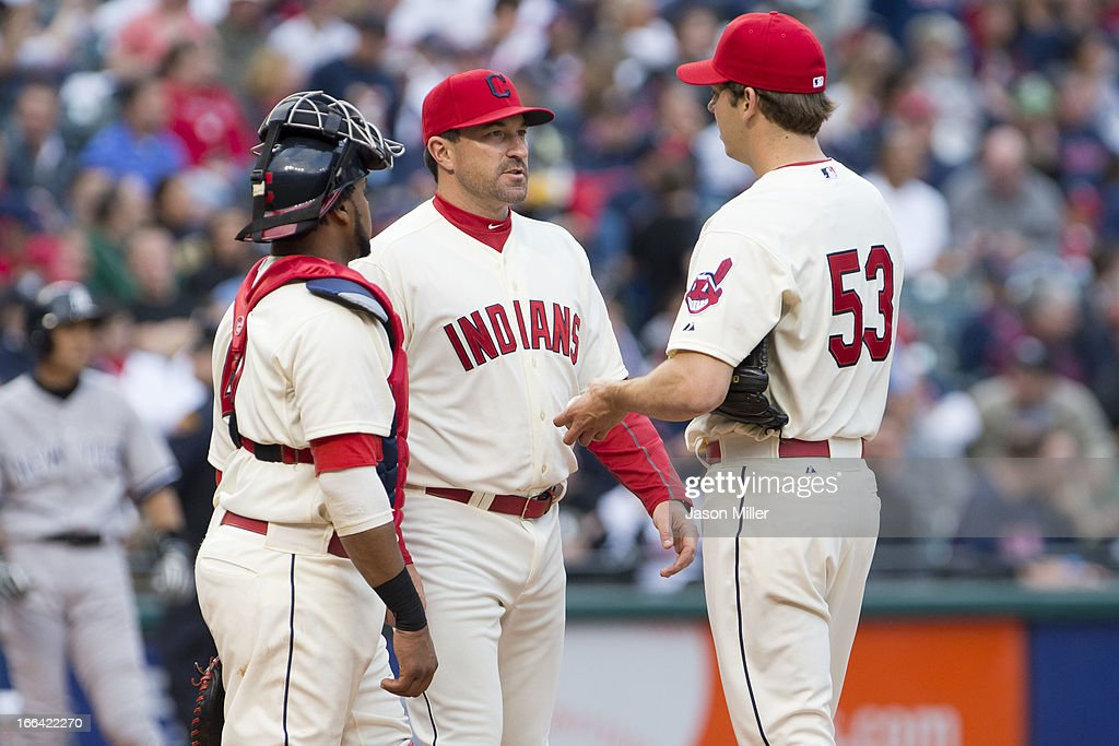 Catcher Carlos Santana #41 and pitching coach pitching coach Mickey Callaway #44 talk with relief pitcher Rich Hill #53 of the Cleveland Indians during the seventh inning against the New York Yankees on opening day at Progressive Field on April 8, 2013 in Cleveland, Ohio.