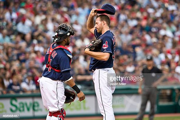 Catcher Carlos Santana of the Cleveland Indians and starting pitcher Zach McAllister of the Cleveland Indians talk strategy on the field during the...