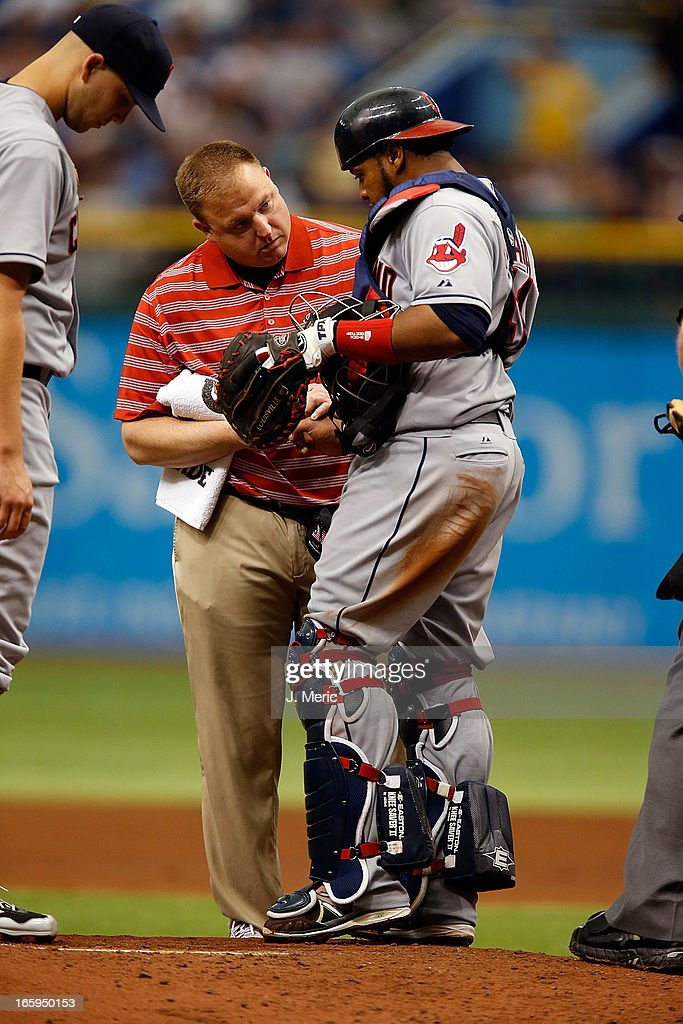 Catcher Carlos Santana #41 of the Cleveland Indians is examined by a trainer after he is hit by a pitch against the Tampa Bay Rays during the game at Tropicana Field on April 7, 2013 in St. Petersburg, Florida.
