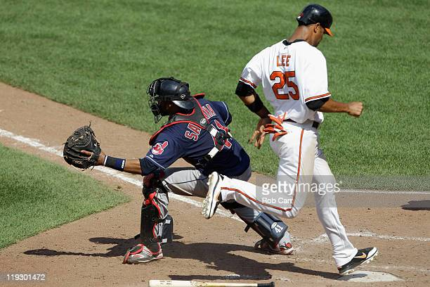 Catcher Carlos Santana of the Cleveland Indians waits for the throw as Derrek Lee of the Baltimore Orioles scores during the seventh inning at Oriole...