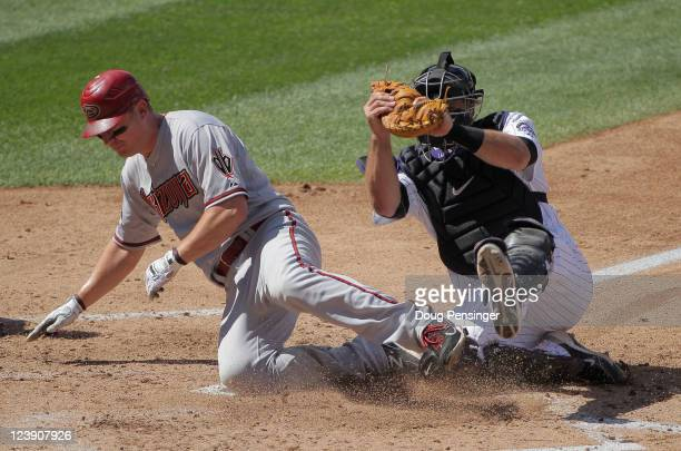 Catcher Chris Iannetta of the Colorado Rockies tags out Geoff Blum of the Arizona Diamondbacks at home as he tried to score on a bunt by Wade Miley...