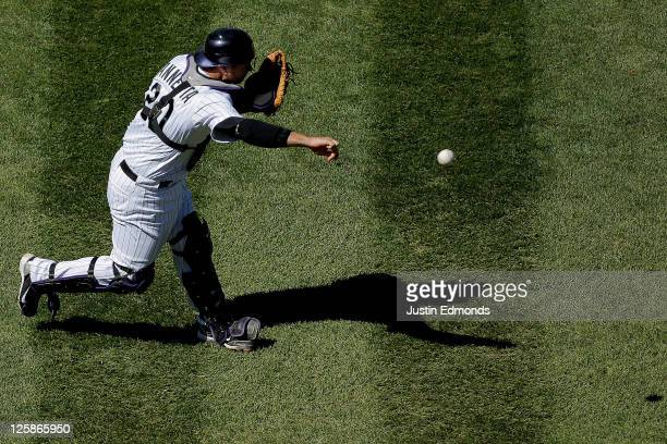 Catcher Chris Iannetta of the Colorado Rockies throws to first base for the first out of the second inning against the San Diego Padres at Coors...