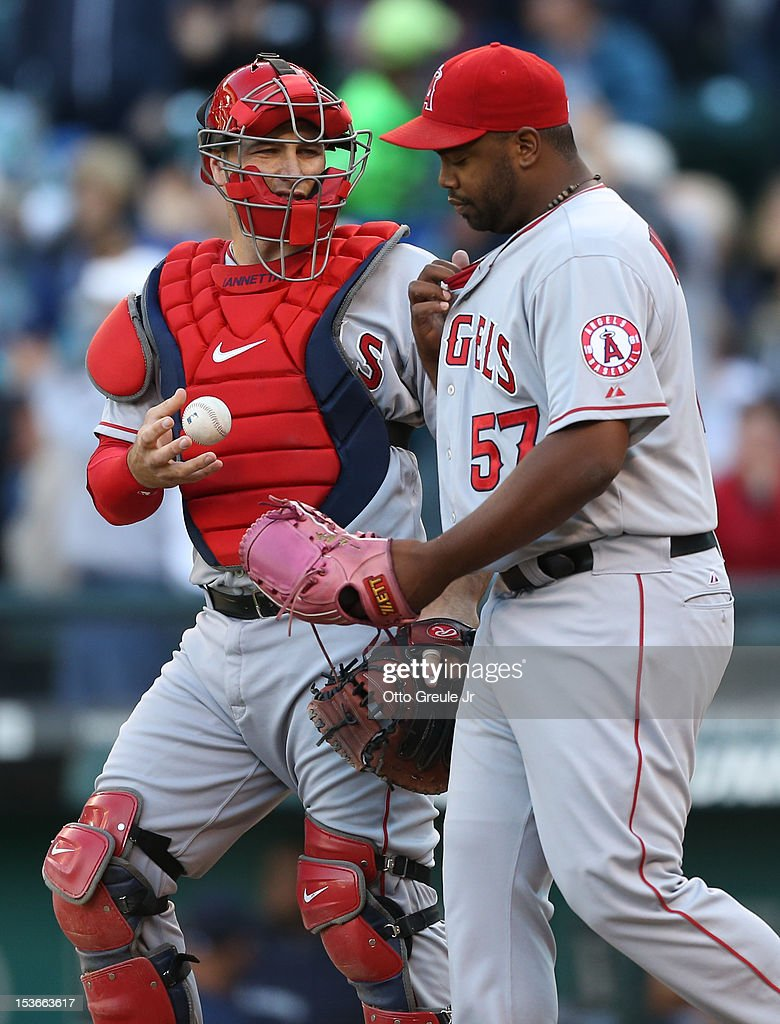 Catcher Chris Iannetta #17 of the Los Angeles Angels of Anaheim talks with relief pitcher Jerome Williams #57 against the Seattle Mariners at Safeco Field on October 3, 2012 in Seattle, Washington.