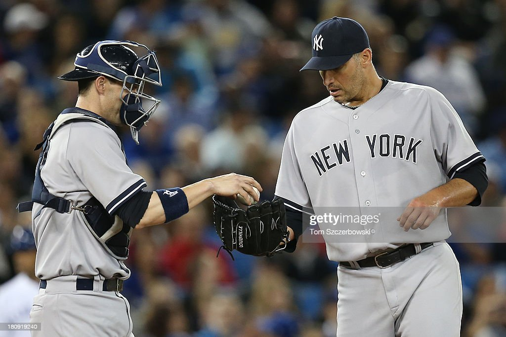 Catcher Chris Stewart #19 of the New York Yankees hands the ball to <a gi-track='captionPersonalityLinkClicked' href=/galleries/search?phrase=Andy+Pettitte&family=editorial&specificpeople=201753 ng-click='$event.stopPropagation()'>Andy Pettitte</a> #46 during MLB game action against the Toronto Blue Jays on September 17, 2013 at Rogers Centre in Toronto, Ontario, Canada.