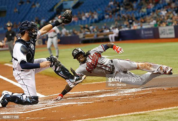 Catcher Curt Casali of the Tampa Bay Rays gets the out at home plate on Cameron Maybin of the Atlanta Braves as Maybin attempts to score off of the...
