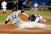 Catcher Curt Casali of the Tampa Bay Rays gets the out at home plate on Chris Iannetta of the Seattle Mariners to end the top of the seventh inning...