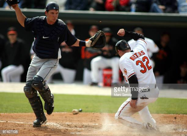 Catcher Dioner Navarro of the Tampa Bay Rays cannot tag out Matt Wieters of the Baltimore Orioles at home at Ed Smith Stadium on March 3 2010 in...