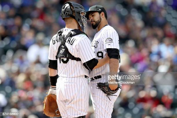Catcher Dustin Garneau and pitcher Carlos Estevez of the Colorado Rockies confer on the mound in the sixth inning against the Washington Nationals at...