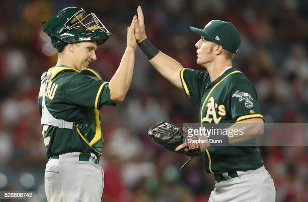 Catcher Dustin Garneau left fielder Mark Canha of the Oakland Athletics celebrate after the game with the Los Angeles Angels of Anaheim at Angel...