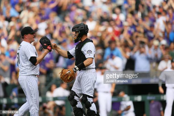 Catcher Dustin Garneau of the Colorado Rockies celebrates the 21 win with closer Jake McGee after defeating the Los Angeles Dodgers 21 on Opening Day...