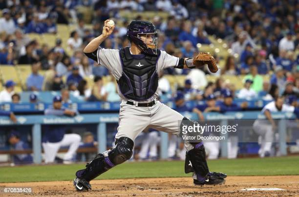 Catcher Dustin Garneau of the Colorado Rockies throws to second base in the middle of the first inning during the MLB game against the Los Angeles...