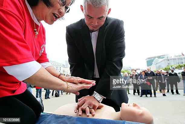 Catcher Eli Whiteside of the San Francisco Giants performs chest compressions on a mannequin while learning CPR on the steps of San Francisco city...