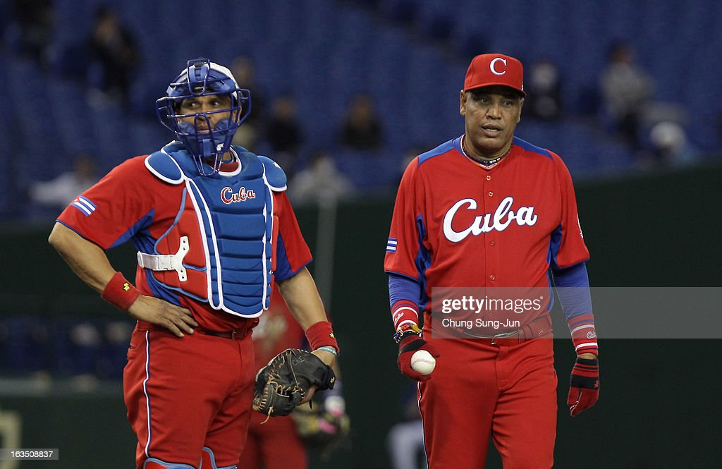 Catcher Eriel Sanchez # 5 and head coach Victor Mesa # 32 confer in the ninth inning during the World Baseball Classic Second Round Pool 1 game between Cuba and the Netherlands at Tokyo Dome on March 11, 2013 in Tokyo, Japan.