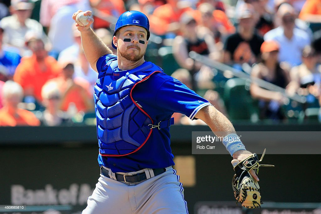 Catcher Erik Kratz of the Toronto Blue Jays throws out a Baltimore Orioles runner at first base at Oriole Park at Camden Yards on June 15 2014 in...