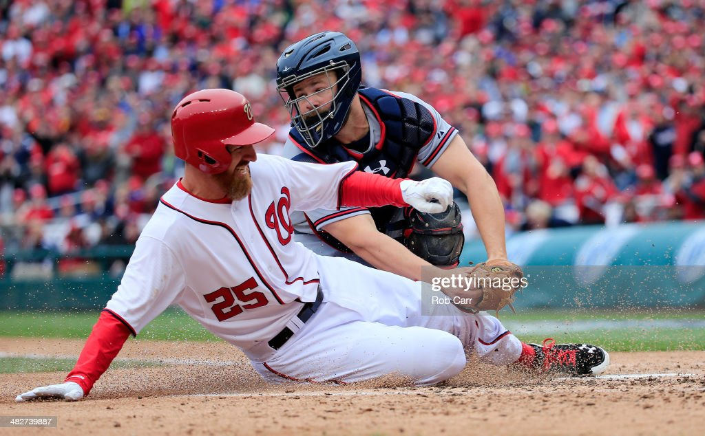 Catcher <a gi-track='captionPersonalityLinkClicked' href=/galleries/search?phrase=Evan+Gattis&family=editorial&specificpeople=8977937 ng-click='$event.stopPropagation()'>Evan Gattis</a> #24 of the Atlanta Braves tags out Adam LaRoche #25 of the Washington Nationals trying to score during the fourth inning of the Nationals home opener at Nationals Park on April 4, 2014 in Washington, DC.