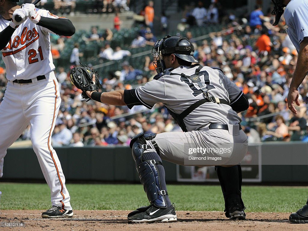 Catcher Francisco Cervelli of the New York Yankees positions himself for a pitch high in the strike zone to Nick Markakis of the Baltimore Orioles...