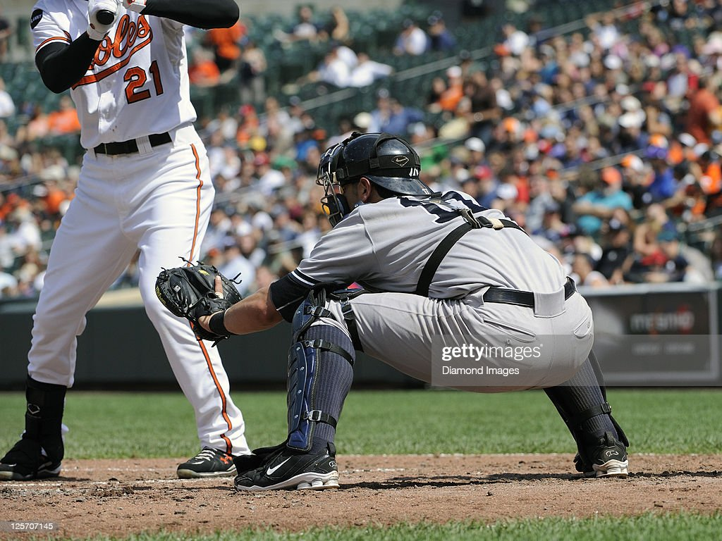 Catcher Francisco Cervelli of the New York Yankees positions himself for a pitch on the outside of the strike zone to Nick Markakis of the Baltimore...
