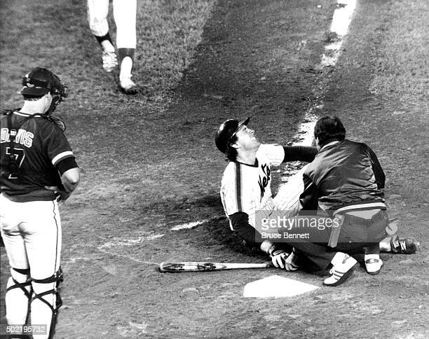 Catcher Gary Carter of the New York Mets sits on the ground in pain after fouling a ball off his leg while the Mets trainer evaluates him during an...